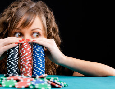 girl peeking over poker chips