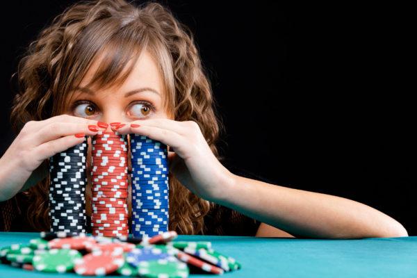 girl peeking over poker chips